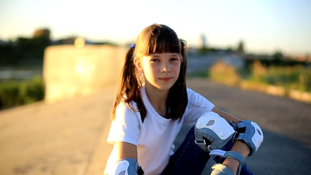 a girl in a white t-shirt with beautiful tails in jeans is skating near the river on a summer evening at sunset. sports, active lifestyle, happy childhood. - maglietta bianca video stock e b–roll