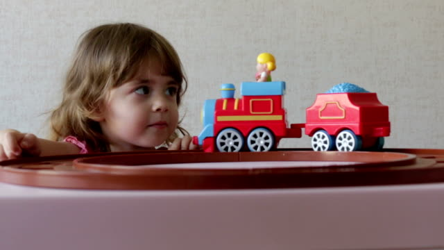 a girl playing with her toy trains on track - giocattolo video stock e b–roll