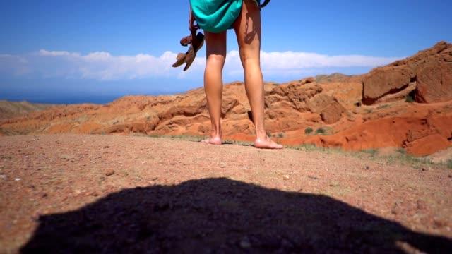 vídeos y material grabado en eventos de stock de una chica está parado descalza en las montañas - moda playera
