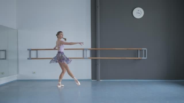 en graciös ballerina dansar i danssalen. skolan för modern och klassisk balett - piruett bildbanksvideor och videomaterial från bakom kulisserna
