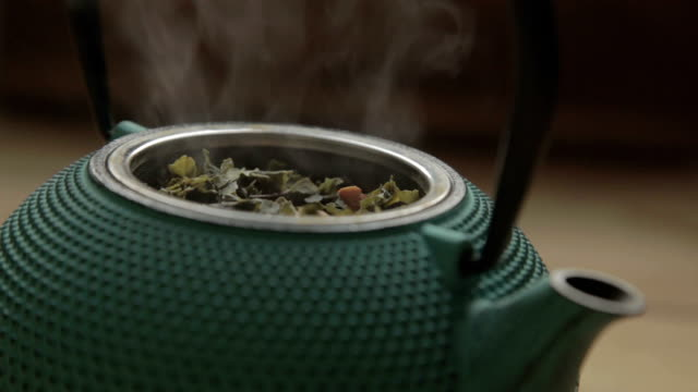 a green traditional tea chest with herb and steam video