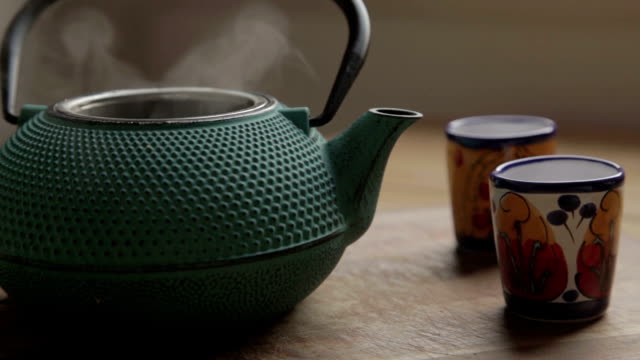 a green traditional tea chest with two colorful cups, open and close the lid with steam a green traditional tea chest with two colorful cups, and a human hand take the lid of the tea chest and comes out the steam, after he close it daylight savings stock videos & royalty-free footage