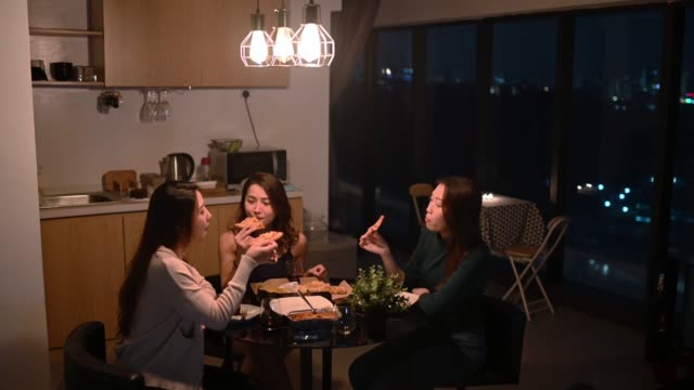 a group of asian chinese female friends having social gathering in apartment eating pizza in dining room at night