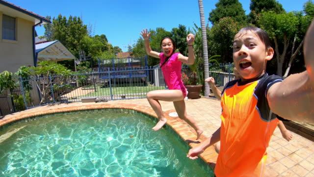 vídeos y material grabado en eventos de stock de pov de un grupo de niños saltando en una piscina - backyard pool