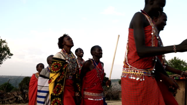 a group of maasai women and men dance in pairs