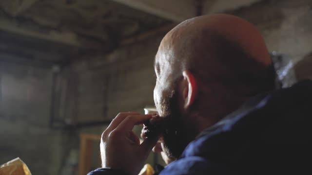 stockvideo's en b-roll-footage met een man met een kale kop en een baard is het drinken van een warme drank uit een wegwerp beker en bijten een broodje - camelia white