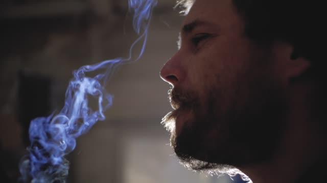 en kille med skägg och en stickad mössa röker en cigarett. marijuana rökning - hasch bildbanksvideor och videomaterial från bakom kulisserna