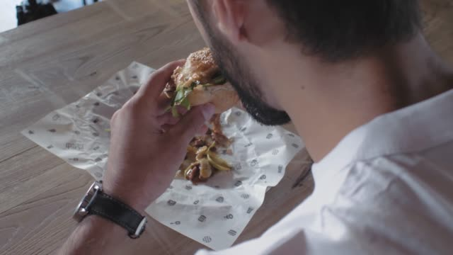 a guy with a beard bites a hamburger sitting at a table in a cafe. man eating a burger. view from above. 4k. 4k video. slow motion. 30 fps