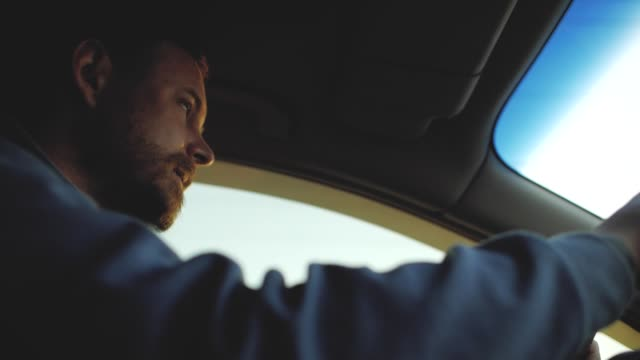 a guy with a beard with beautiful eyes is driving a car. sun rays in the window - спортсмен стоковые видео и кадры b-roll