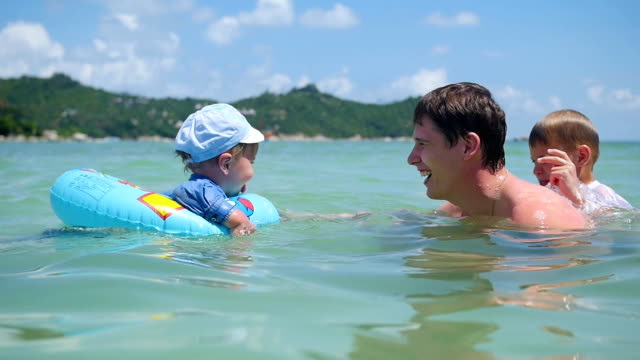 a guy with kids plays having fun in the sea - solo bambini maschi video stock e b–roll