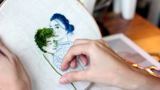 vídeos de stock e filmes b-roll de a hand stitching needle and thread making embroidery artwork for couple portrait. - fundo oficina