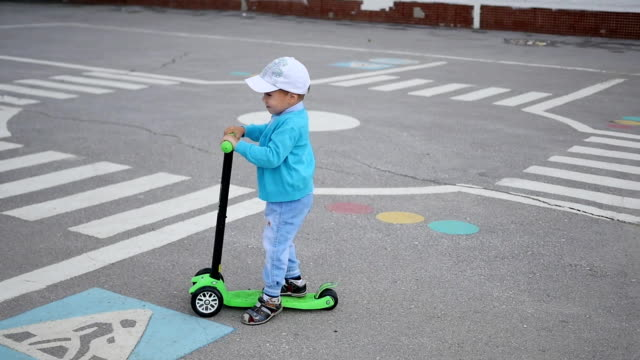 a happy child rides his scooter in the park.fun outdoors - solo bambini maschi video stock e b–roll