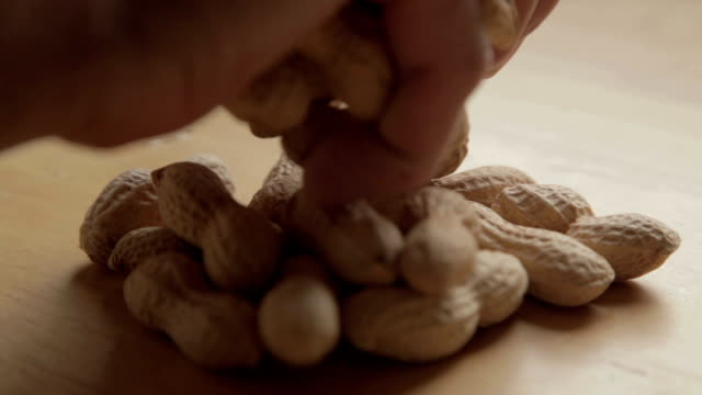 a human hand create a small block of Peanuts In Shell on a table a human hand create a small block of Peanuts In Shell on a table daylight savings stock videos & royalty-free footage