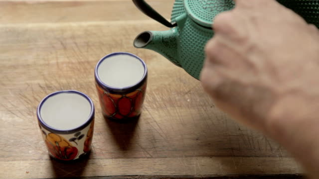a human hand put hot water with a tea chest inside of two colorful ceramic cups a human hand put hot water with tea chest inside of two colorful ceramic cups daylight savings stock videos & royalty-free footage