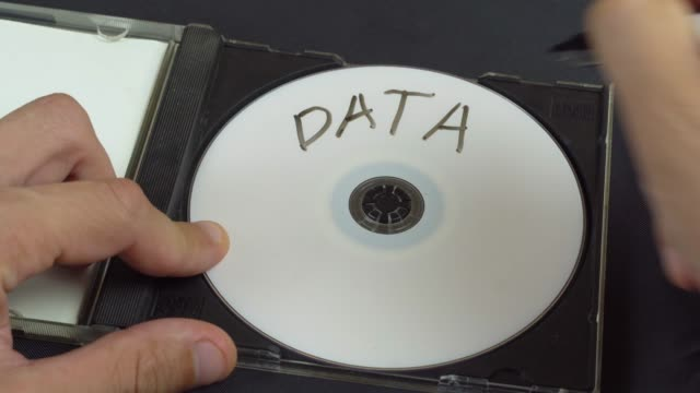 a human hand writes data on a white CD. Marker.