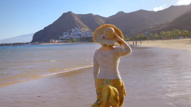 a lady in a hat walks along a tropical beach at sunset A woman walks along the beach at sunset and breathing the sea air caribbean stock videos & royalty-free footage