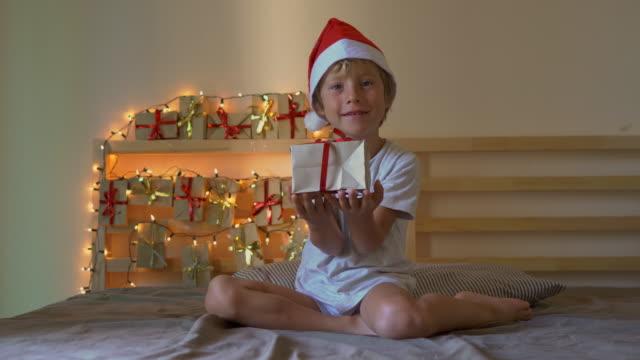 vidéos et rushes de un petit garçon ouvrant un cadeau d'un calendrier de l'avent qui est suspendu sur un lit qui est allégé avec des lumières de noel. se préparer pour le concept de noel et du nouvel an. concept de calendrier de l'avent - calendrier de l'avent