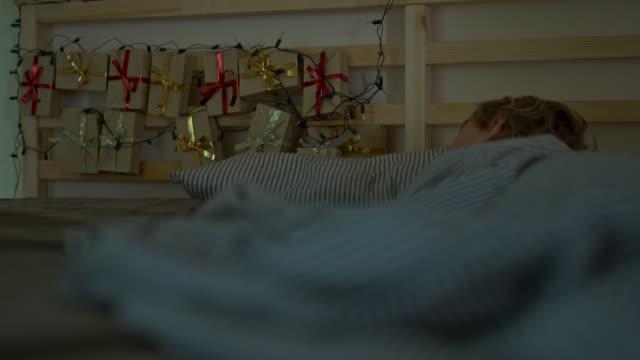 vidéos et rushes de un petit garçon qui dort dans son lit avec un calendrier de l'avent s'éclaircit avec des lumières de noel brille sur le dos de son lit. se préparer pour le concept de noel et du nouvel an. concept de calendrier de l'avent - calendrier de l'avent