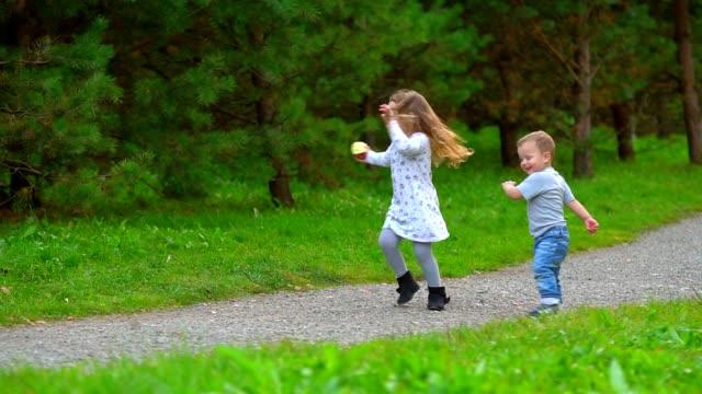 ein kleines mädchen und ein junge, tanzen, drehen im herbst park. - smiley stock-videos und b-roll-filmmaterial