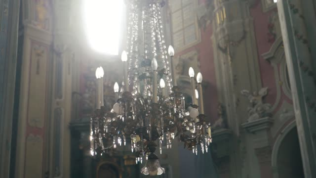 a luxurious chandelier hangs in the middle of a catholic cathedral on the background of frescoes. - candeliere video stock e b–roll