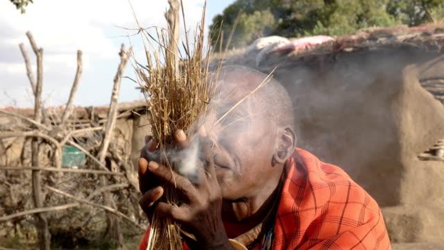 vídeos de stock e filmes b-roll de a maasai warrior starts fire the traditional way at a manyatta in kenya - quénia
