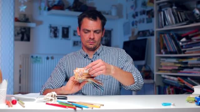 ein mann an einem tisch im büro legt geld in form eines ventilators - billionär stock-videos und b-roll-filmmaterial