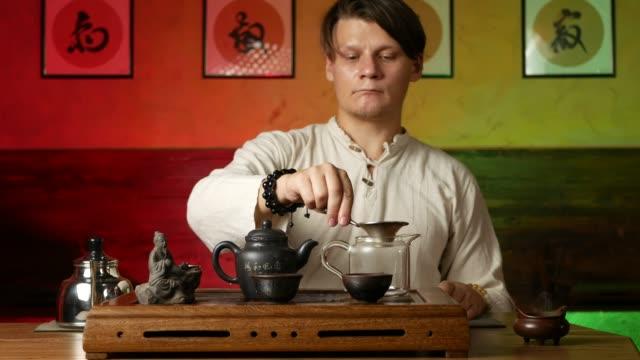 vídeos de stock e filmes b-roll de a man brews pu-erh tea according to traditional chinese customs - coffee table