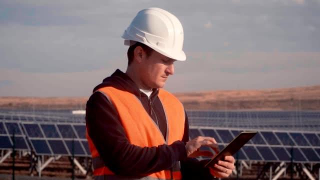 stockvideo's en b-roll-footage met een man in een ingenieur van de helm op de achtergrond van een zonne-energiecentrale houden een digitale tablet - gebruind