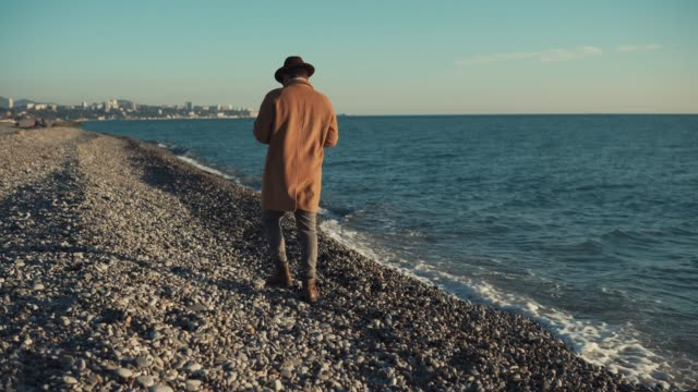 a man in a long coat and hat walks along the shore, waves are beating video