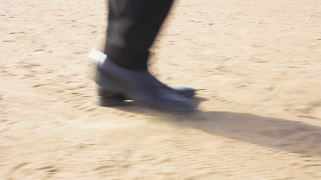 a man in a suit and shoes rides along the beach