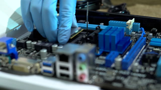 a man in blue latex gloves collects chips. production of modern computers. the hands of a person set the ditali. FullHD video