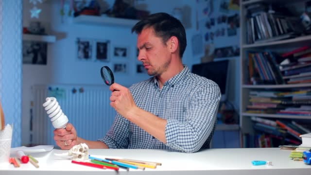a man looks at a light bulb through a magnifying glass, shows surprise