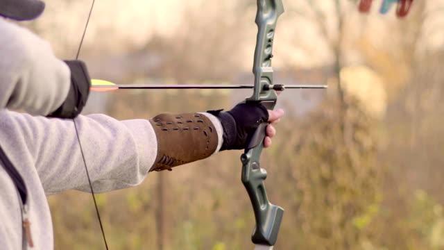 vidéos et rushes de un homme tire un arc - tir à l'arc