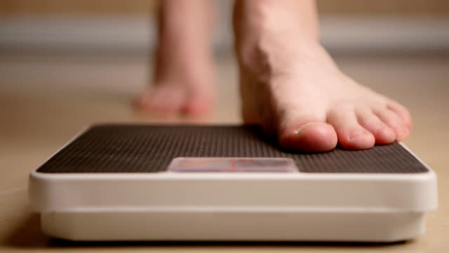 a man standing on weight scale - вес стоковые видео и кадры b-roll