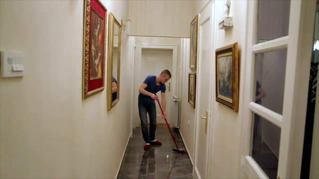 a man sweeping the floor with broomstick at home video