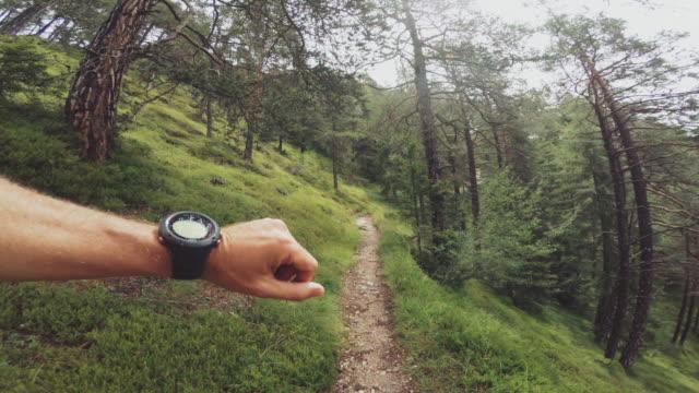 vídeos de stock e filmes b-roll de pov of a man trail running and checking sportwatch - ângulo