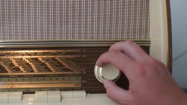a man twists the handle of a radio receiver, tunes in a radio wave
