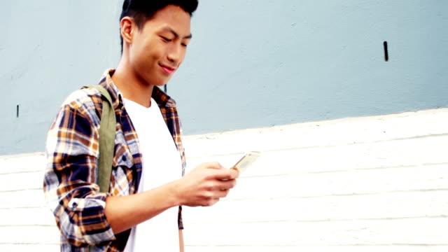 vídeos de stock e filmes b-roll de a man walking, laughing and watching his smartphone - homem casual standing sorrir