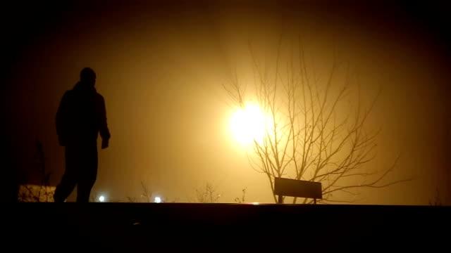 vídeos de stock e filmes b-roll de a man walks on a foggy night - capuz