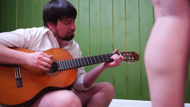 a man with a beard by the green wall and plays the guitar. red high-heeled shoes