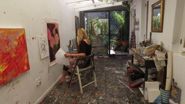 vídeos de stock e filmes b-roll de a mature woman painting in her art studio at home. - avental