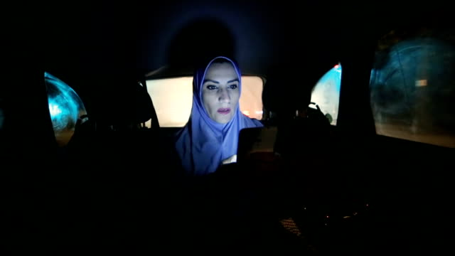 a modern Arab woman rides in a car  at night video