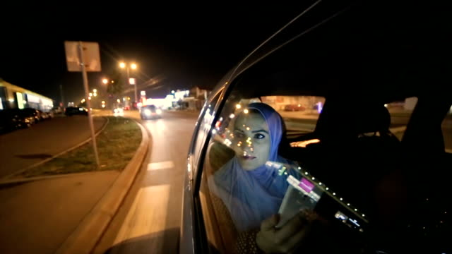 a modern Arab woman rides in a taxi at night video