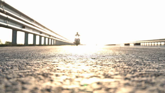 a motorcyclist in the rays of the sun passing along the road past the camera - bike tire tracks video stock e b–roll