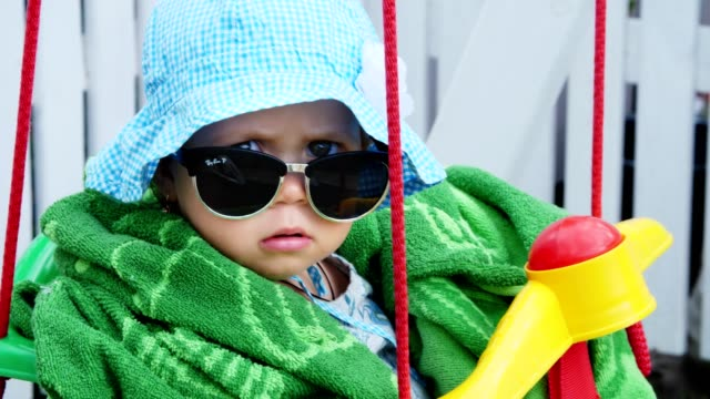 a one-year-old girl in a panama and sunglasses, like an important lady, sits in the children's swing and swings, in the summer, in the garden