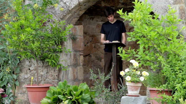 a poet reads a book placed on a bookrest in a beautiful  garden - poetry -  man video