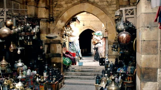 a porter carries goods at khan el khalili market - египет стоковые видео и кадры b-roll