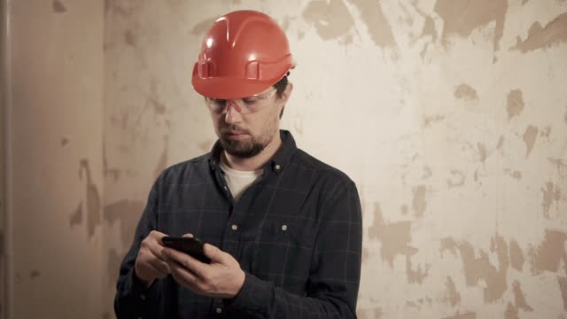 a portrait of a foreman who checks the completed work on the list on the phone - vídeo