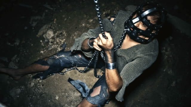 a prisoner in chains is closed in the basement where a little light penetrates video