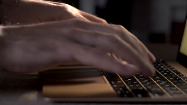 a programmer or writer types on a laptop keyboard video